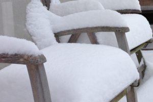 Dicke Schneeschicht auf den Gartenstühlen.